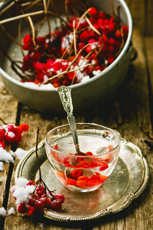 guelderrose: fresh berries of a guelder-rose in a glass cup on a wooden table. style rustic.  the image is tinted