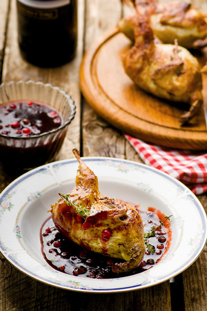 cowberry: the baked quails with cowberry sauce. style rustic. selective focus Stock Photo
