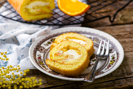 swiss roll: swiss roll with whipped cream and orange cream. style rustic. selective focus