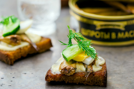 tinned: toasts with tinned sprats. traditional Russian festive dish. style vintage. selective focus