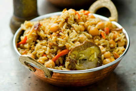 arroces: pilaf vegetariana con garbanzos y setas en un taz�n indio de cobre. enfoque selectivo