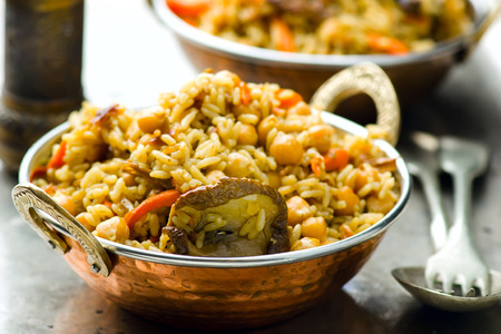 arabian food: vegetarian pilaf with chick-pea and mushrooms in a copper Indian bowl. selective focus