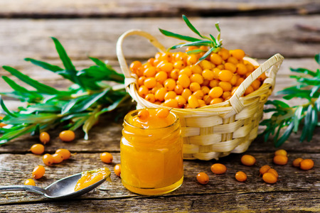 seabuckthorn: jam from a sea-buckthorn and berry of an organic sea-buckthorn in a basket. style rustic . selective focus