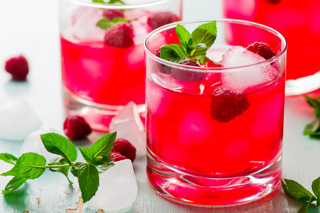 cold drink with raspberry, mint and ice in a glass. style vintage. selective focus Imagens