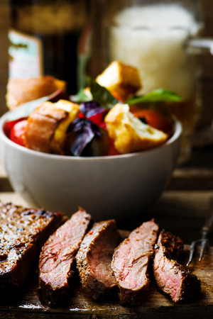 flank: flank steak  with tomato salad and glass of beer. style vintage.  selective focus Stock Photo