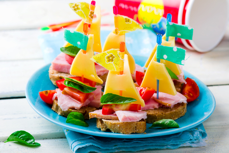 ham: ham and cheese sandwiches in the form of ships for a childrens holiday. selective focus