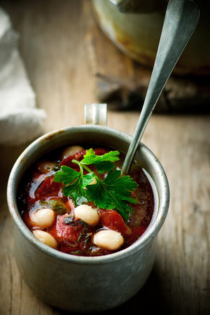 beans soup: bean soup and sausages and metal mug. style rustic. selective focus