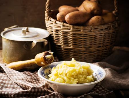Tłuczone ziemniaki i surowego ziemniaka w koszu. Styl rustic.selective ostrości