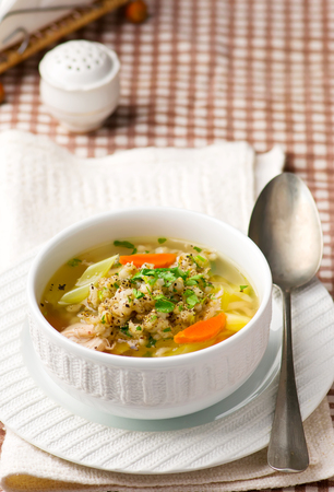 groat: chicken soup with barley groat in a white bowl. style . selective focus Stock Photo