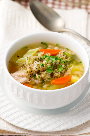 groat: chicken soup with barley groat in a white bowl. style. selective focus