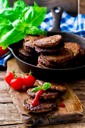 fritters: fritters from a liver with tomato sauce. style rustic. selective focus Stock Photo