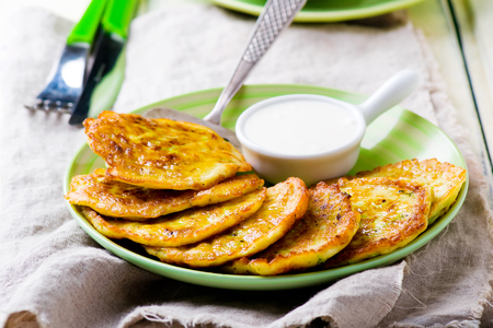vegetable marrows fritters with sour cream on a green plate. selective focus Stock Photo