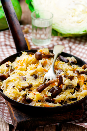Cabbage solyanka with mushrooms in a vintage frying pan. style rustic. selective focus