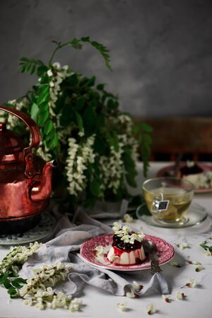 pannacotta with acacia flowers and cherry sauce..selective focus
