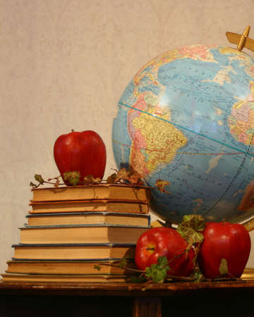Still life of books, apples, and globe