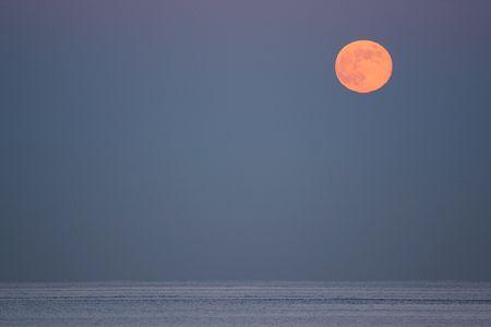 December full moon rising over the ocean