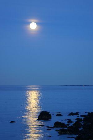 December full moon lighting up the ocean near the rocks