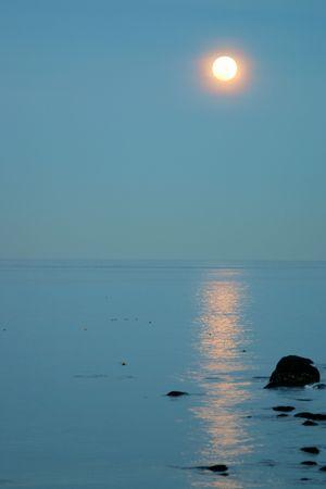 Pinkish full moon rising over the ocean