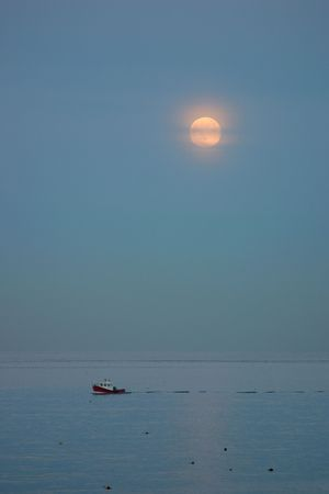 lobster boat: Red lobster boat travelling under the moon glow Stock Photo