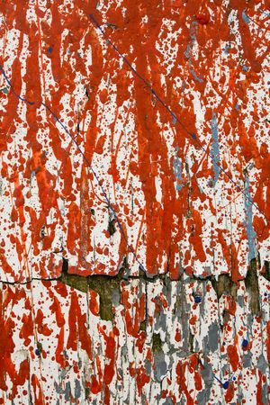 Orange and Gray paint splattered on a white cracked piece of plywood Imagens