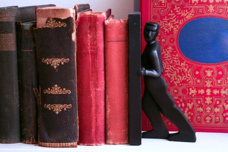 Red and black books on a shelf with a man bookend