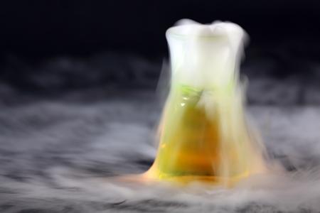 Erlenmeyerr kolf met droog ijs en groene vloeistof Stockfoto