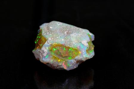 Kostbare opaal op een spiegel en een zwarte achtergrond.