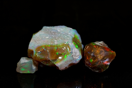 Precious opal on a mirror and a black background.