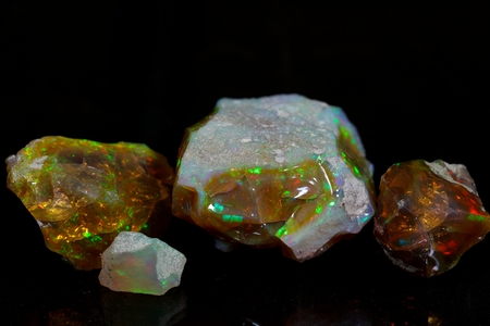 opal: Precious opal on a mirror and a black background.