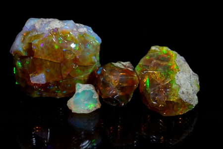 amorphous: Precious opal on a mirror and a black background.