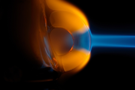Macro photography of melting glass in the flame of a gas torch.