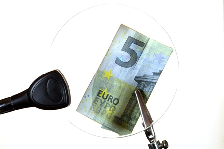 ambiguity: A Euro Note behind a magnifying glass. Stock Photo