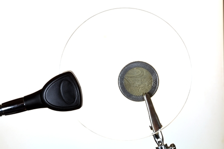 ambiguity: A Euro coin behind a magnifying glass