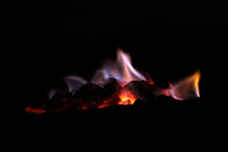 blue flames: Glowing charcoal with blue flames and a black background.