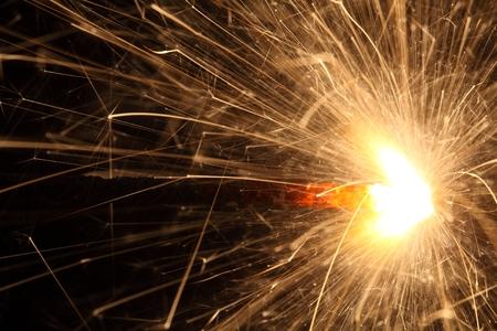 Macro photo of firework sparkles with black background.