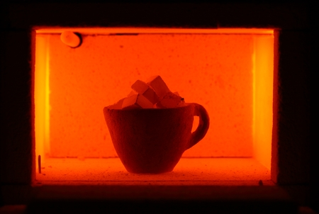 to muffle: A glowing muffle furnace with a ceramic pott and limestone cubes.