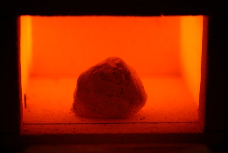 furnace: A glowing muffle furnace with a limestone rock. Stock Photo