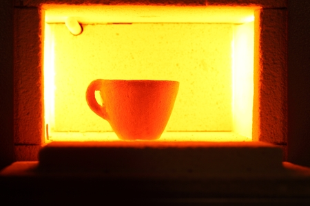 to muffle: A glowing muffle furnace with a ceramic pott.