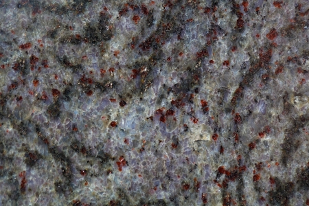 labradorite: Macro photo of the surface of a gneiss rock containing with red minerals.
