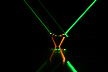 laser beam: A green laser beam reflection in different colored glass. Stock Photo