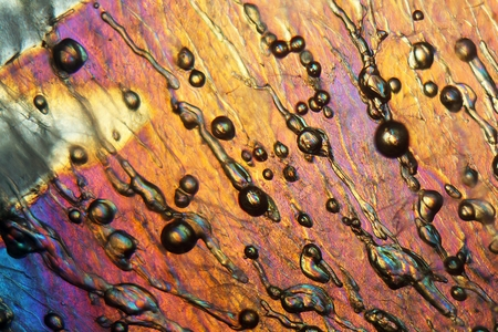 Air bubbles in ice under the microscope with a magnification of 80 times and in polarized light. Stock Photo