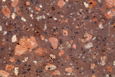 Surface of a porphyry rhyolite rock from central Europe, Saxony-Anhalt. The rock contains fragments of feldspars, quartz and amphibole minerals in a fine grained matrix.