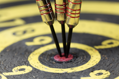 Macro of dart arrows in an old dartboard.