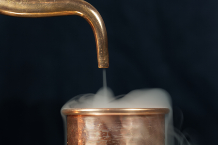 A copper pipe of a distillery with steam.