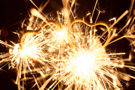 Macro photo of a burning sparkler in form of a heart. Stock Photo