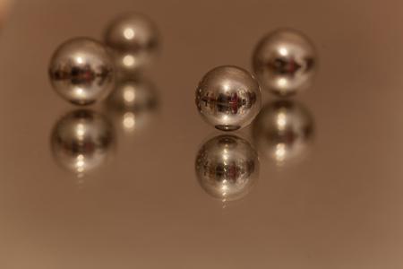 Macro photo of steel balls on a mirror. Stock Photo