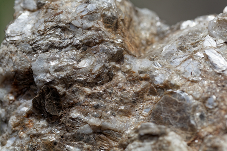 Macro photo of weathered mica minerals in coarse grained quartz rock. Stock Photo