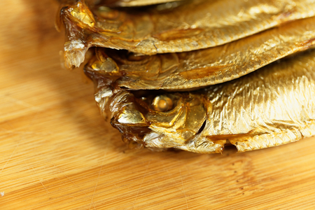 Smoked European sprats, Sprattus sprattus, on a wooden background.