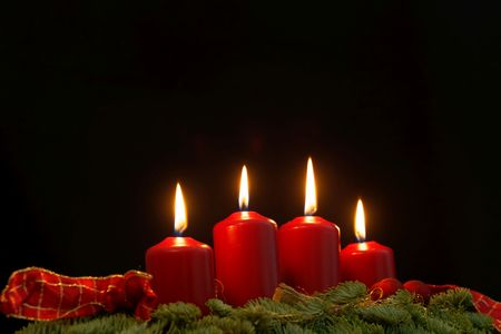 Red candles of an Advent wreath with fir branches and a black background.