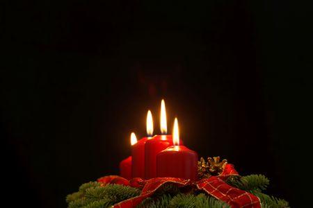 Velas rojas de una corona de Adviento con ramas de abeto y un fondo negro.